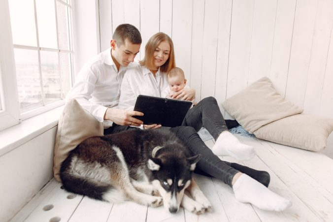 Couple sitting with baby in arms and dog lying at feet